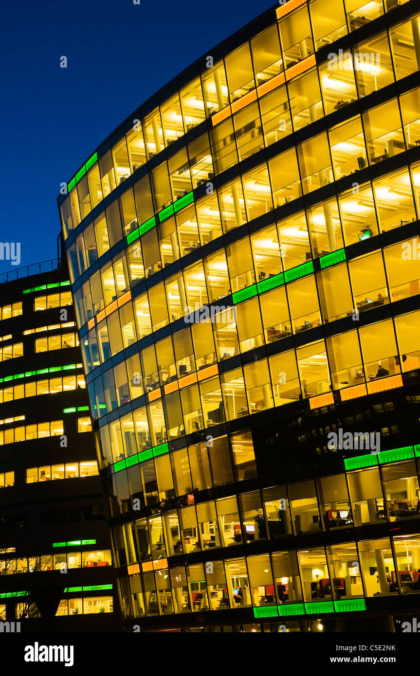 Low angle view of illuminated open-plan office building with windows against blue sky - Stock Image