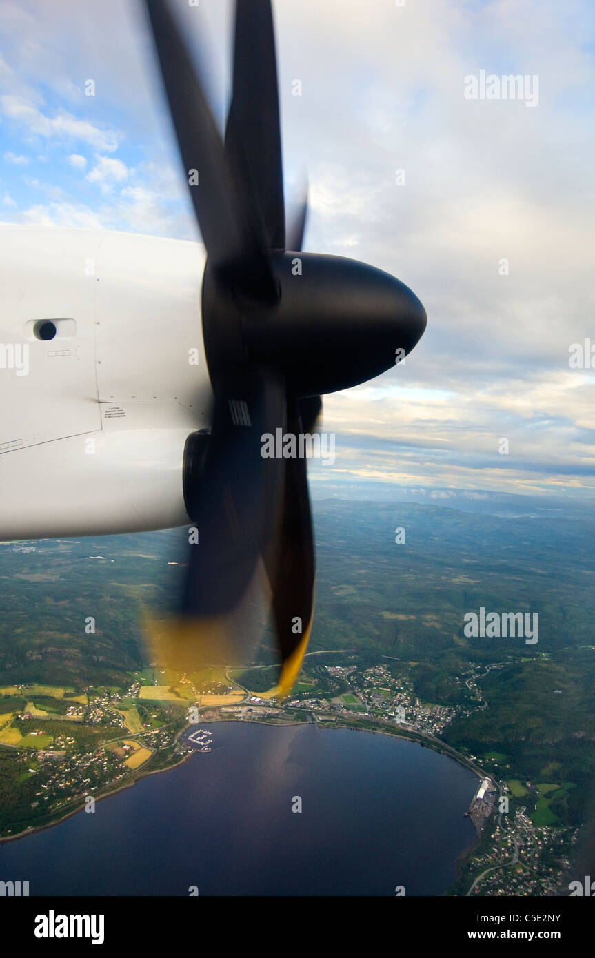 Close-up of airplane propeller over city and against clouds - Stock Image