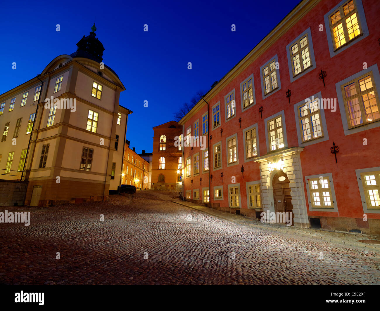 Svea Court of Appeal against blue sky with cobblestone courtyard in foreground at night in Stockholm - Stock Image