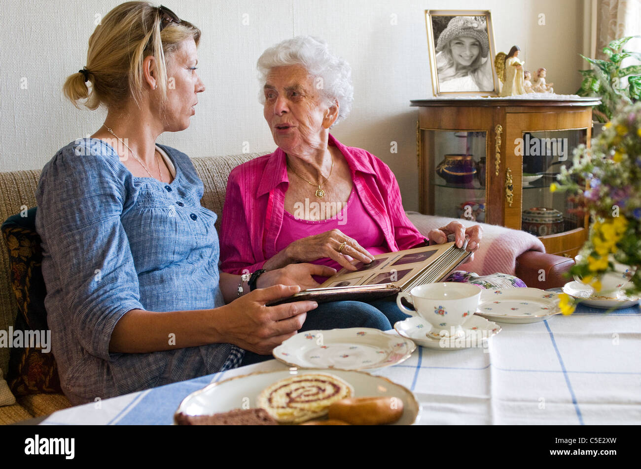 Woman on coffee visit with grandma at home - Stock Image
