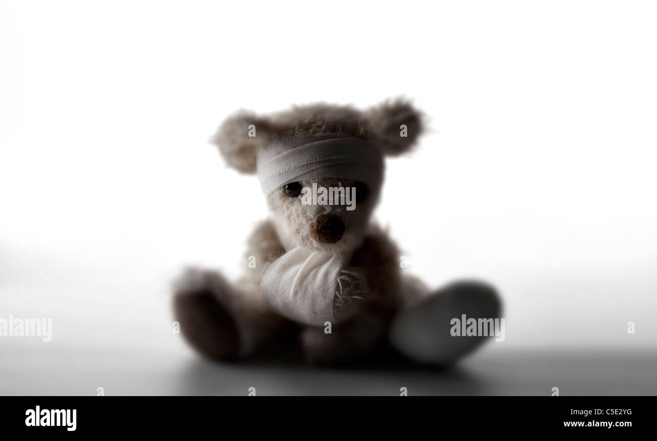 Close-up of a teddy bear with bandage around head and hand sitting against white background - Stock Image