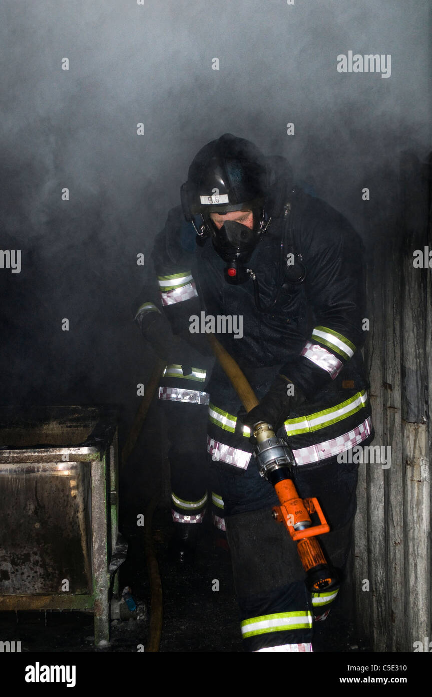 View of a firefighter in protective wear on duty - Stock Image