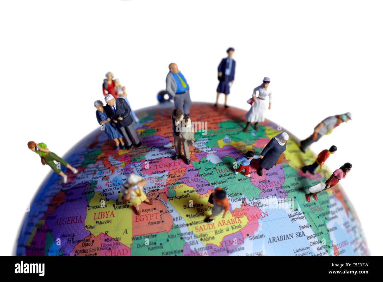Diverse human miniatures on the globe against white background - Stock Image