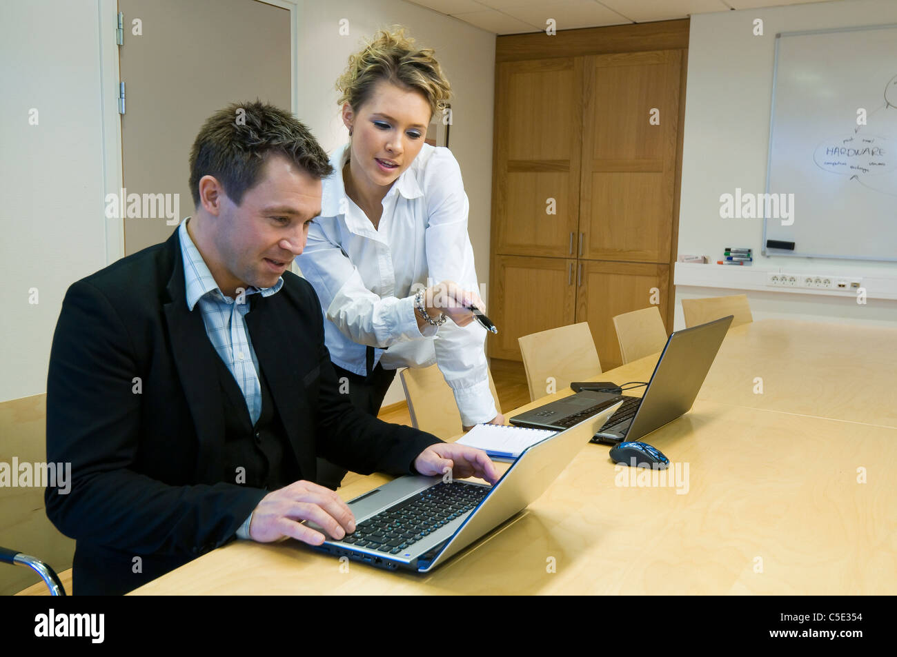 Male and female colleagues discussing a topic on the internet at office desk - Stock Image
