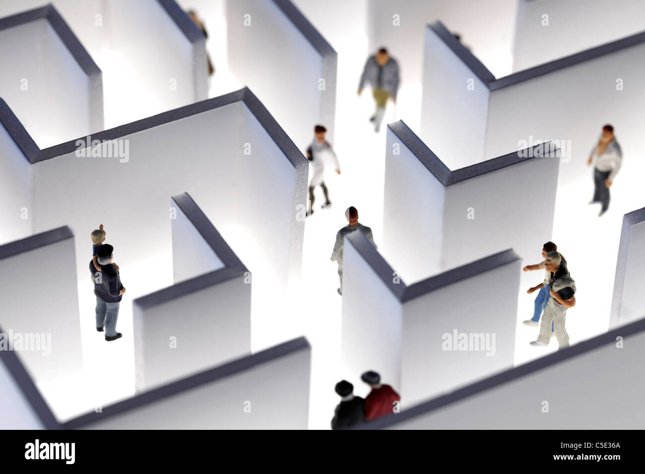 Close-up of human miniatures walking in maze against white background - Stock Image