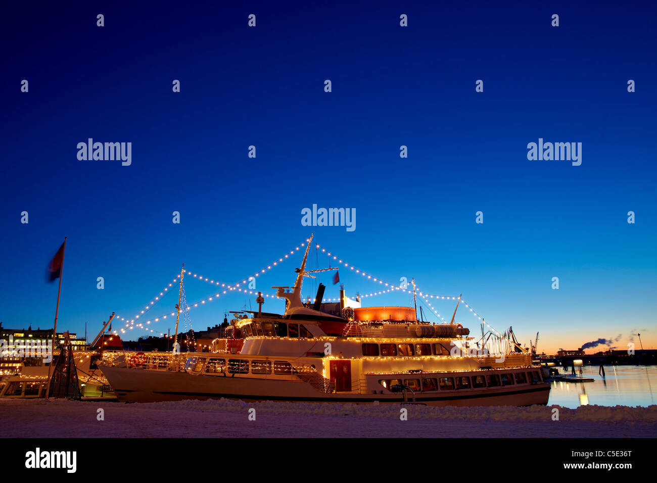 Side shot of an illuminated ship against the blue sky at dusk in Goteborg - Stock Image