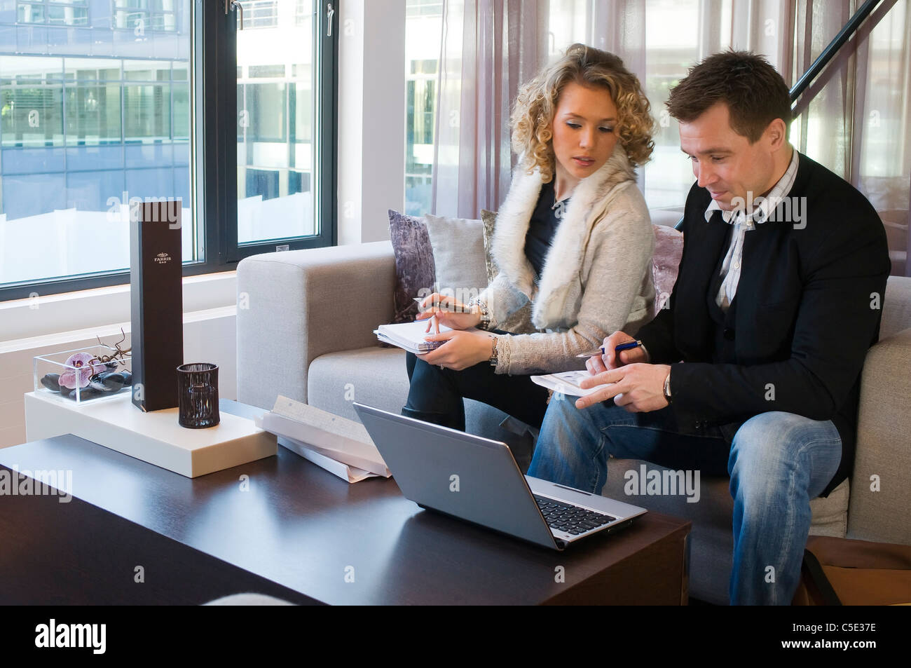 Male and female colleagues writing documents with laptop in the office lounge - Stock Image