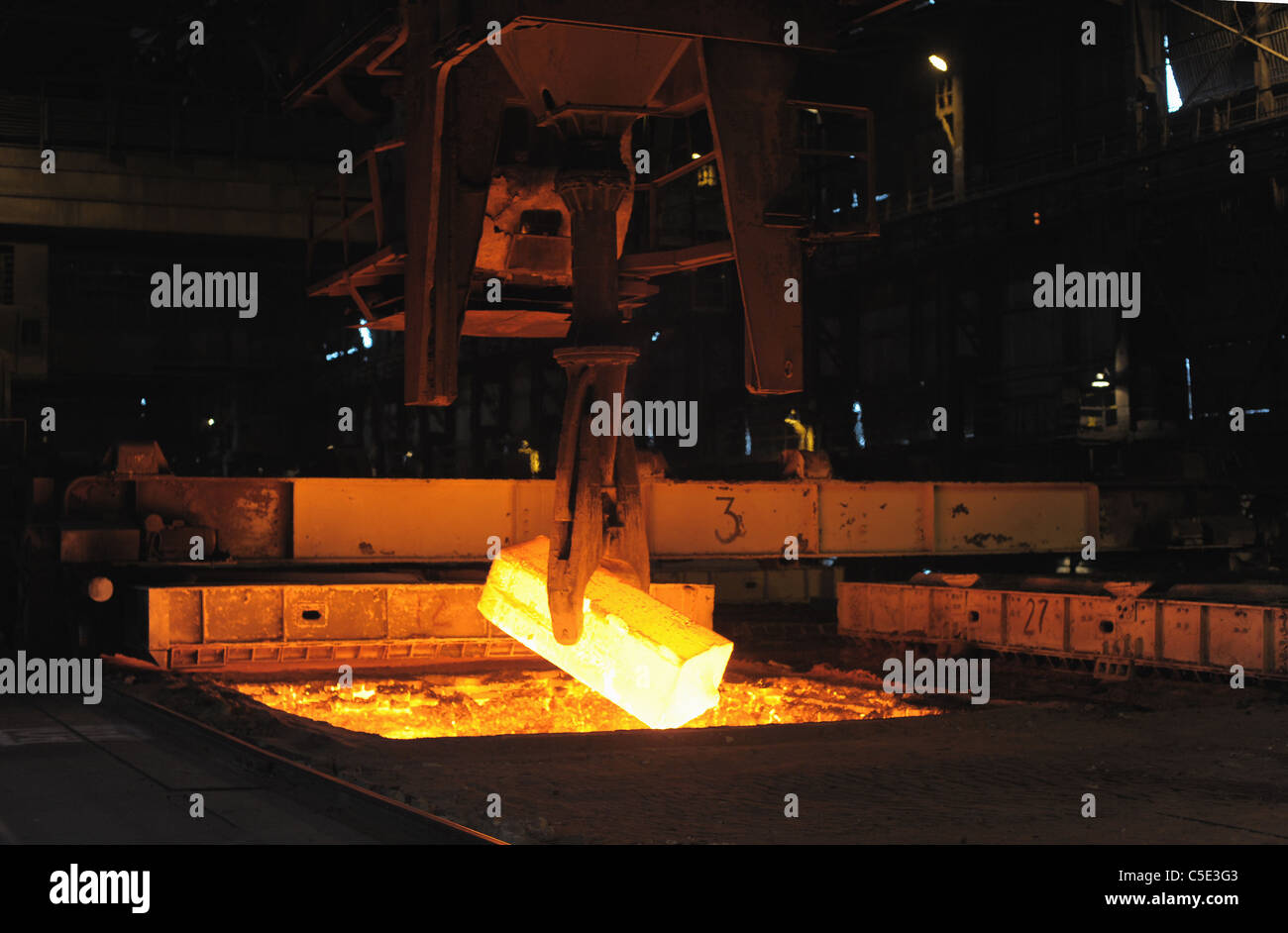 The heated steel pigs the crane from takes out furnaces - Stock Image