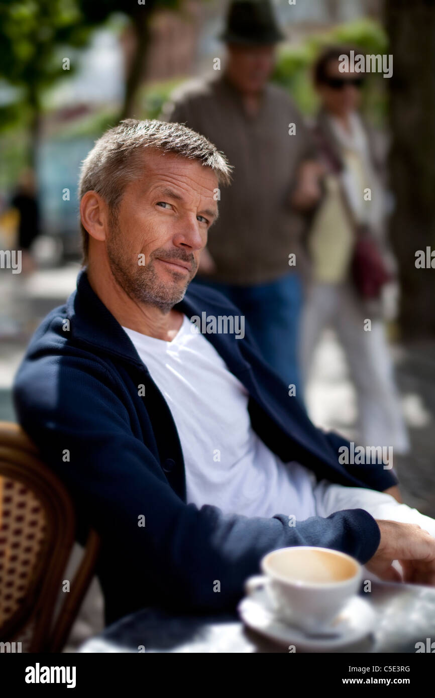 Middle-aged man at the street café with blurred people in the background Stock Photo