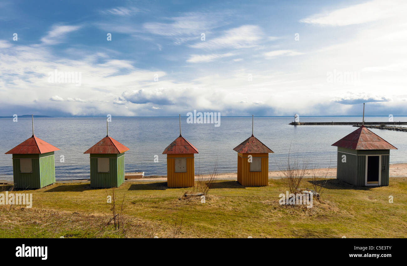 Bathing huts in a row by the peaceful sea against cloudy sky - Stock Image