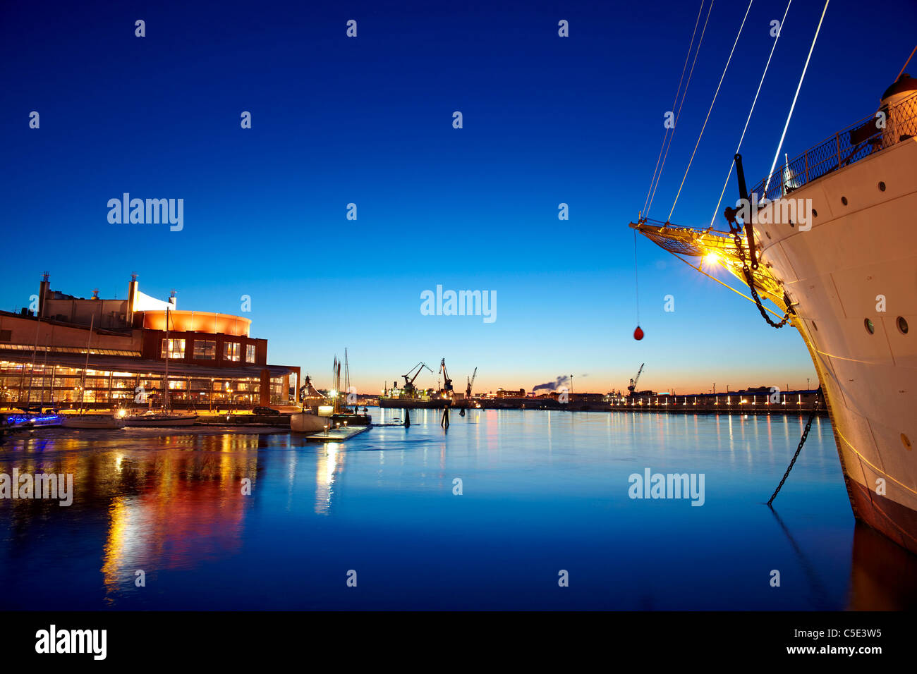 Cropped ship anchored in peaceful lake with Gothenburg opera in the background at dusk - Stock Image
