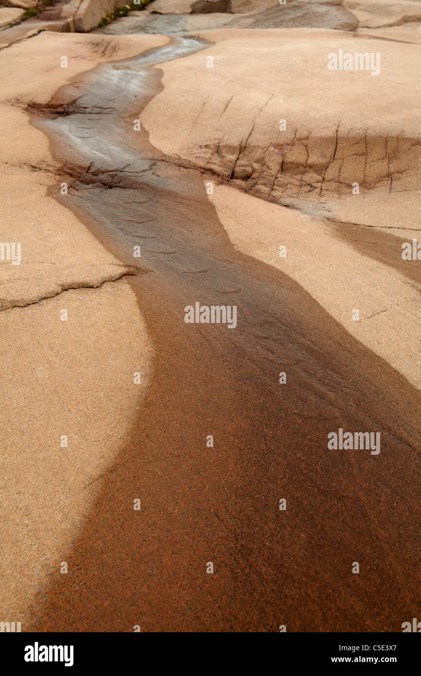 Close-up of running water over bedrock - Stock Image