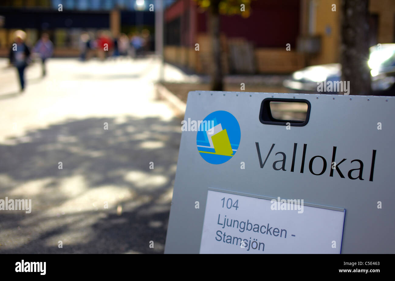 Close-up of polling signboard against the blurred street - Stock Image