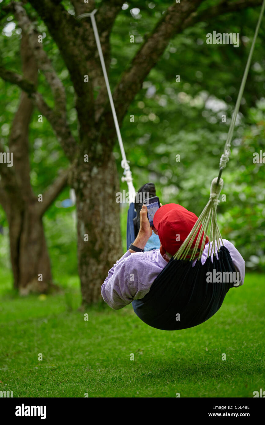 Man lying in a hammock with mobile phone over the meadow with trees in background - Stock Image
