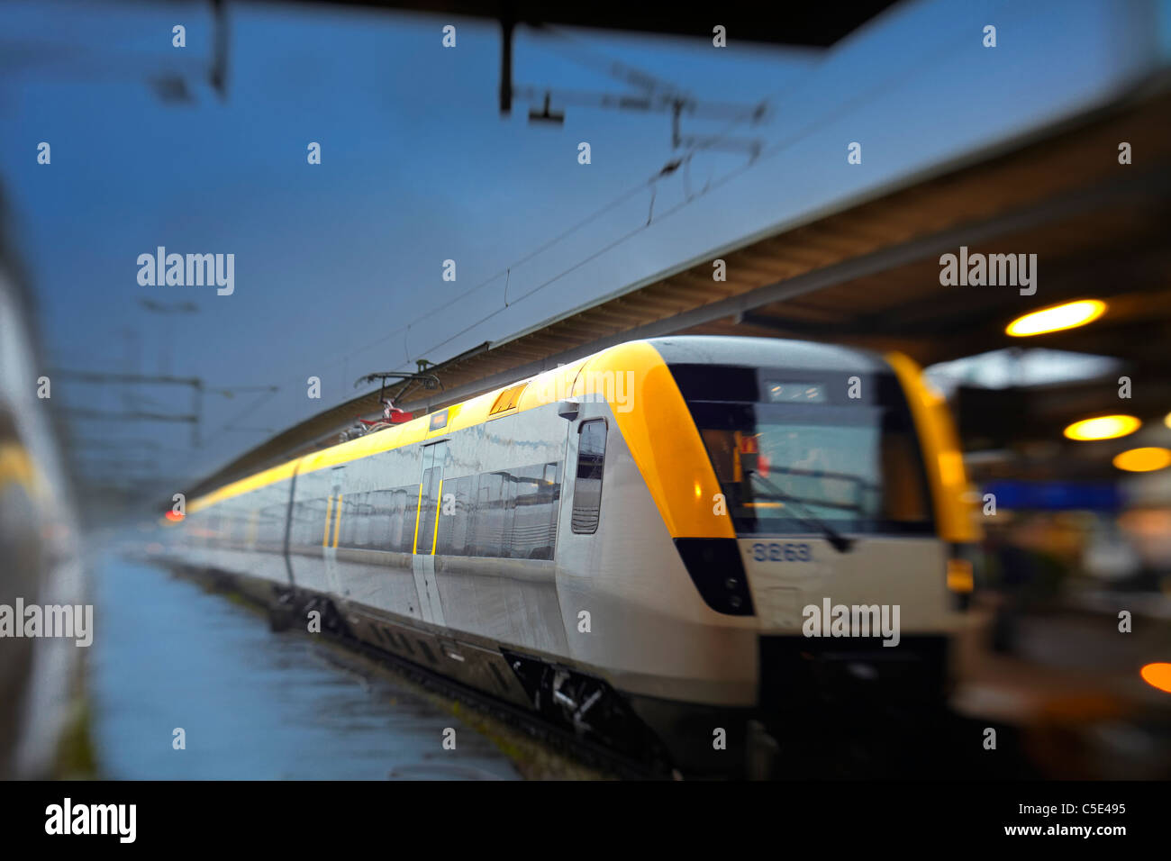 Express train arriving at the railway platform station against blue sky - Stock Image