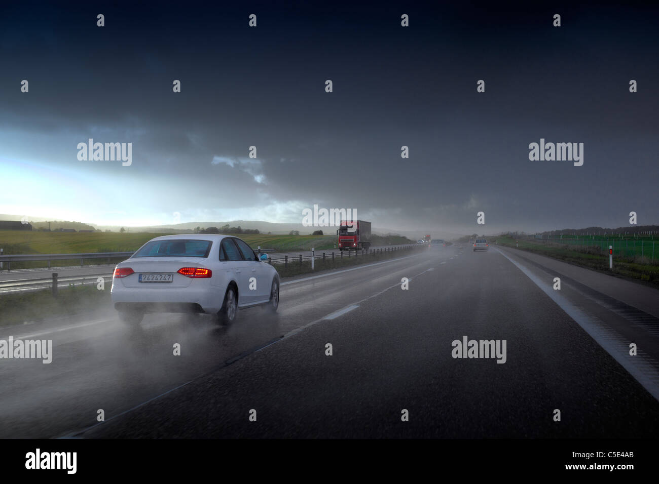 View of vehicles on the asphalt road against cloudy sky on a rainy day - Stock Image