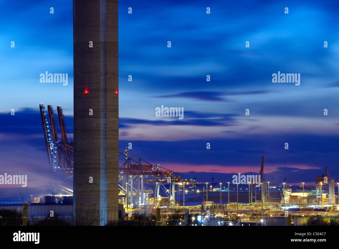 Close-up of a chimney with cranes and factories in the background at dusk, Gothenburg - Stock Image