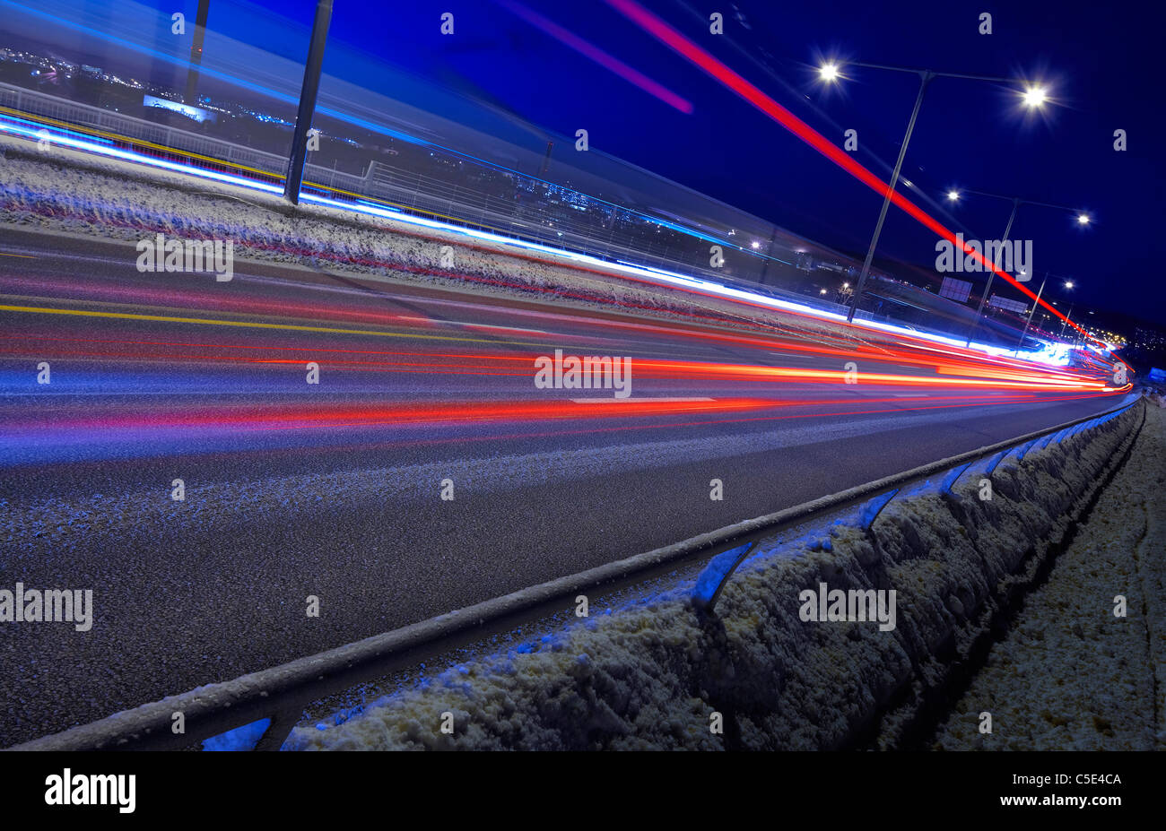 Tilt shot of blurred red light trails on road in winter at night - Stock Image