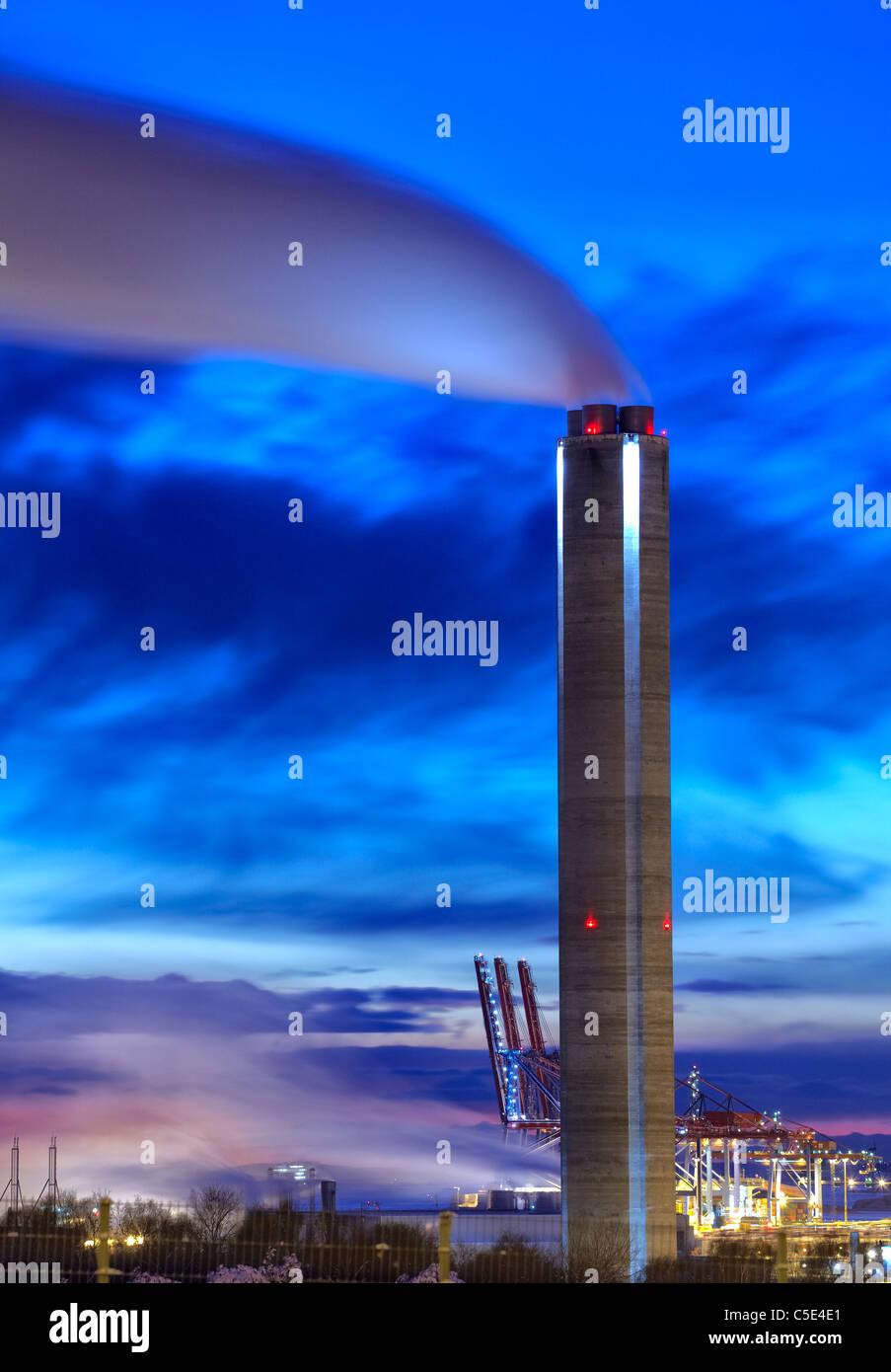 Factory chimney emitting smoke against dramatic blue sky at dusk Stock Photo