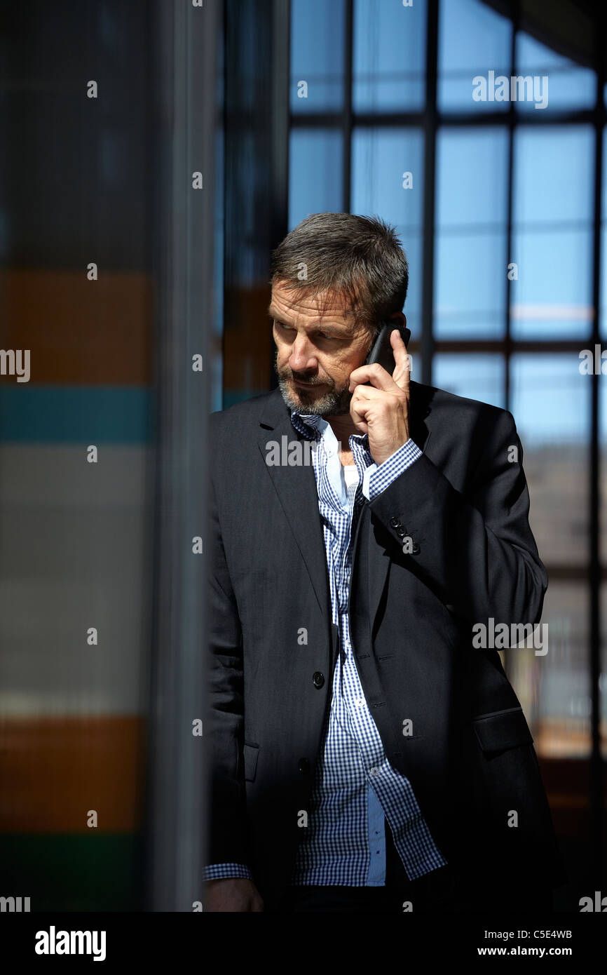 Well dressed middle-aged businessman using a cell phone - Stock Image