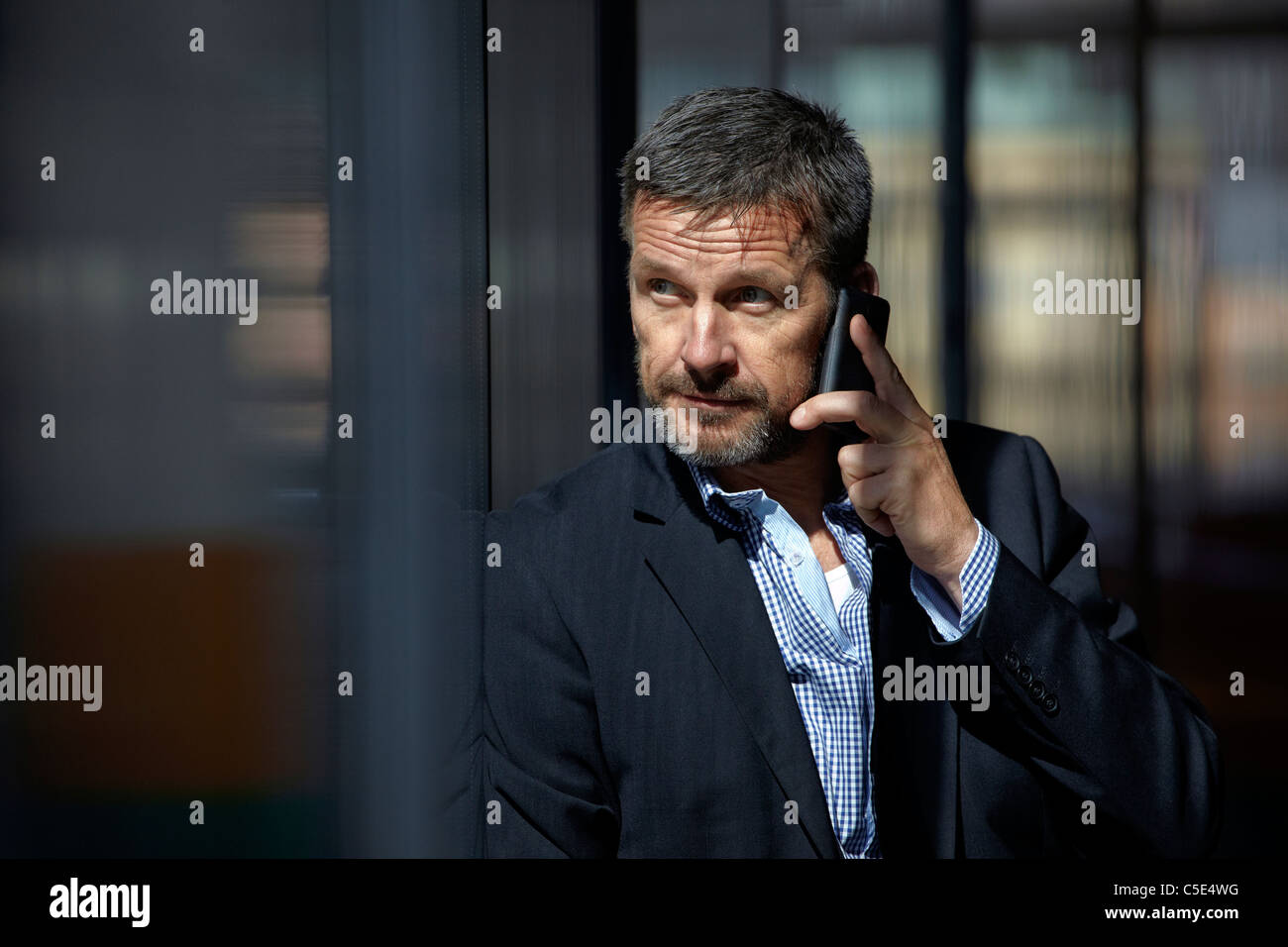 Middle-aged businessman using mobile phone against blurred background - Stock Image