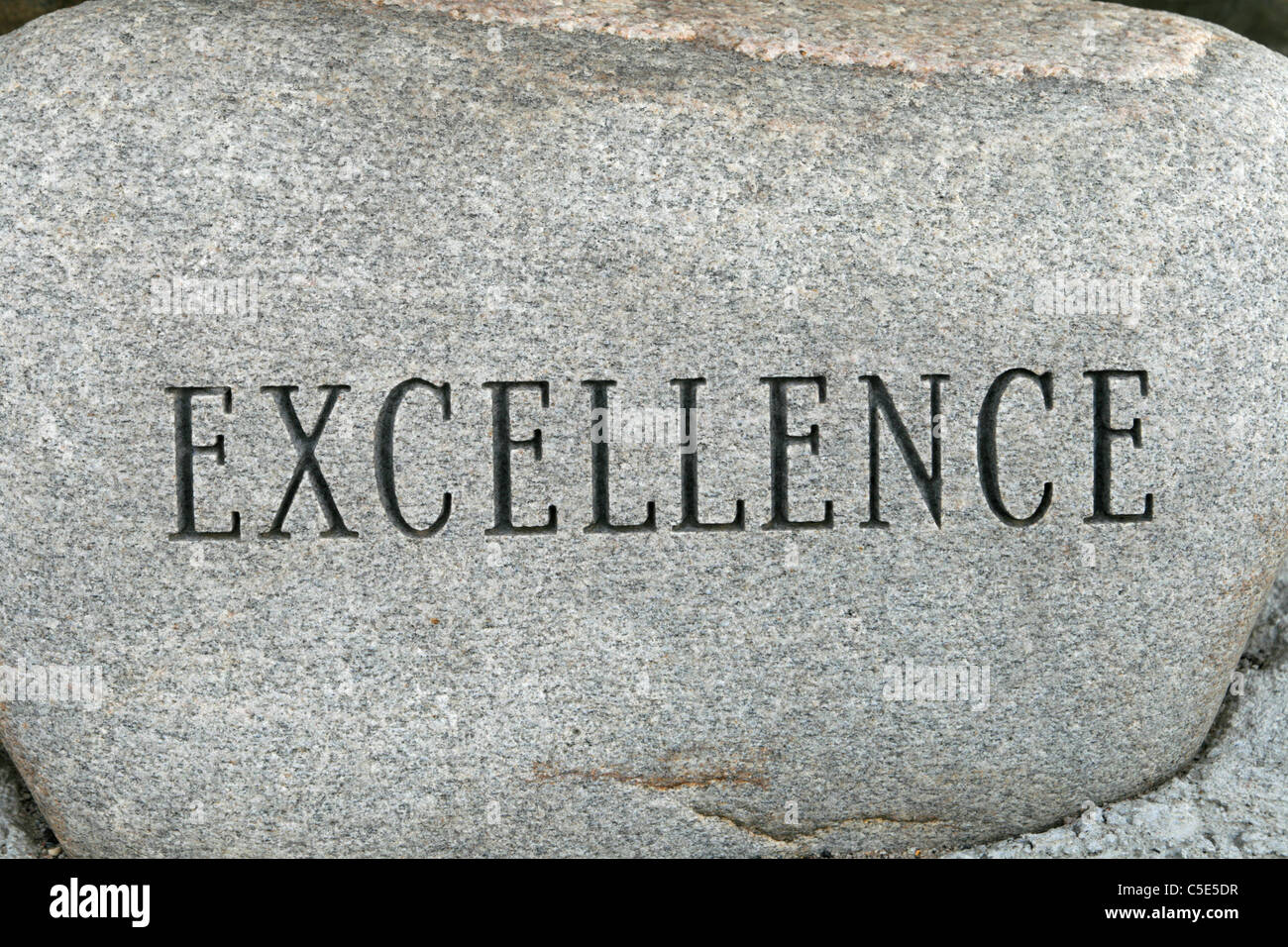 the word excellence carved onto a granite cobble stone - Stock Image