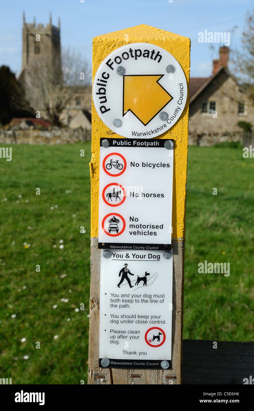 Public Footpath Sign, No Bicycles, No Horses, No Motorised Vehicles Signs, and Village Church, Long Compton, Oxfordshire - Stock Image
