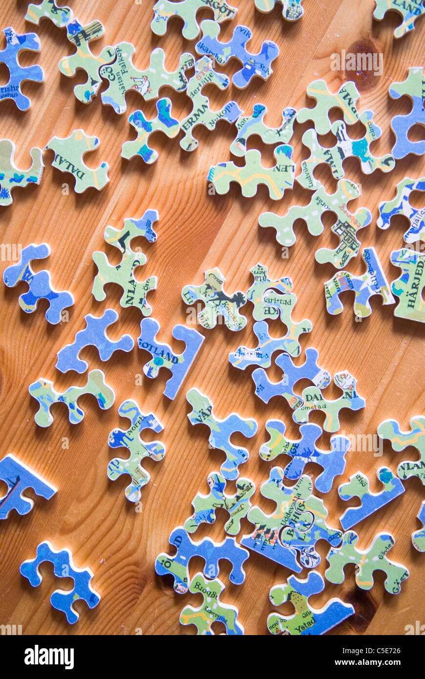 Close Up Of Scattered Pieces Of Jigsaw Puzzle On Wooden Floor Stock