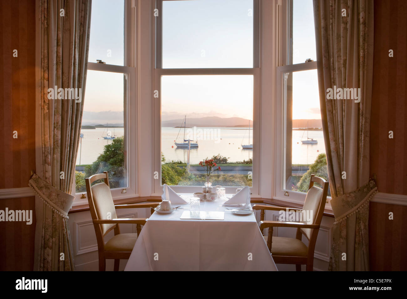 Guest house dining room overlooking loch at sunset, Scotland, UK - Stock Image