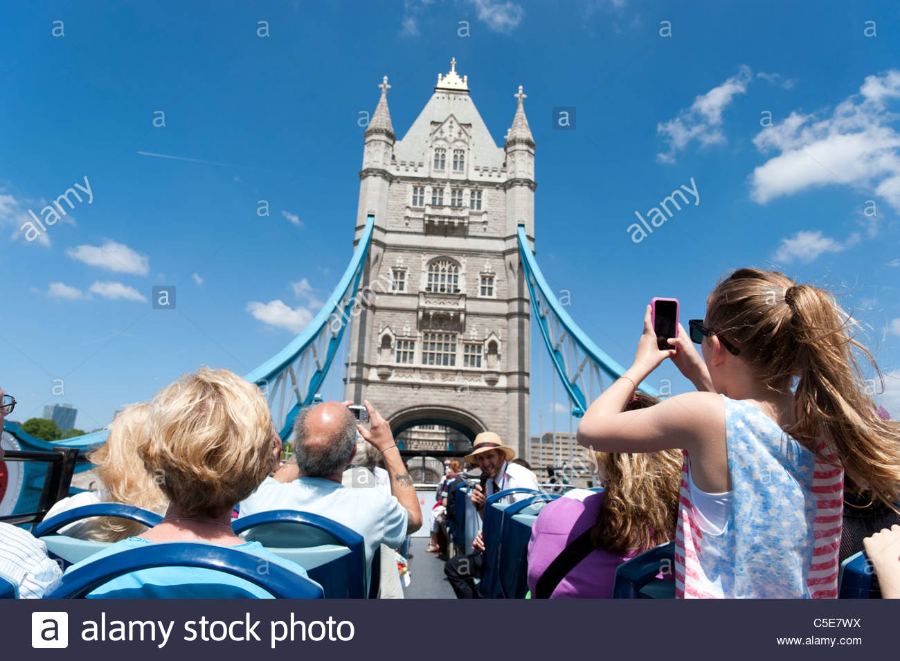 Tourists on open top double decker Original London tour bus crossing Tower Bridge, London, UK - Stock Image