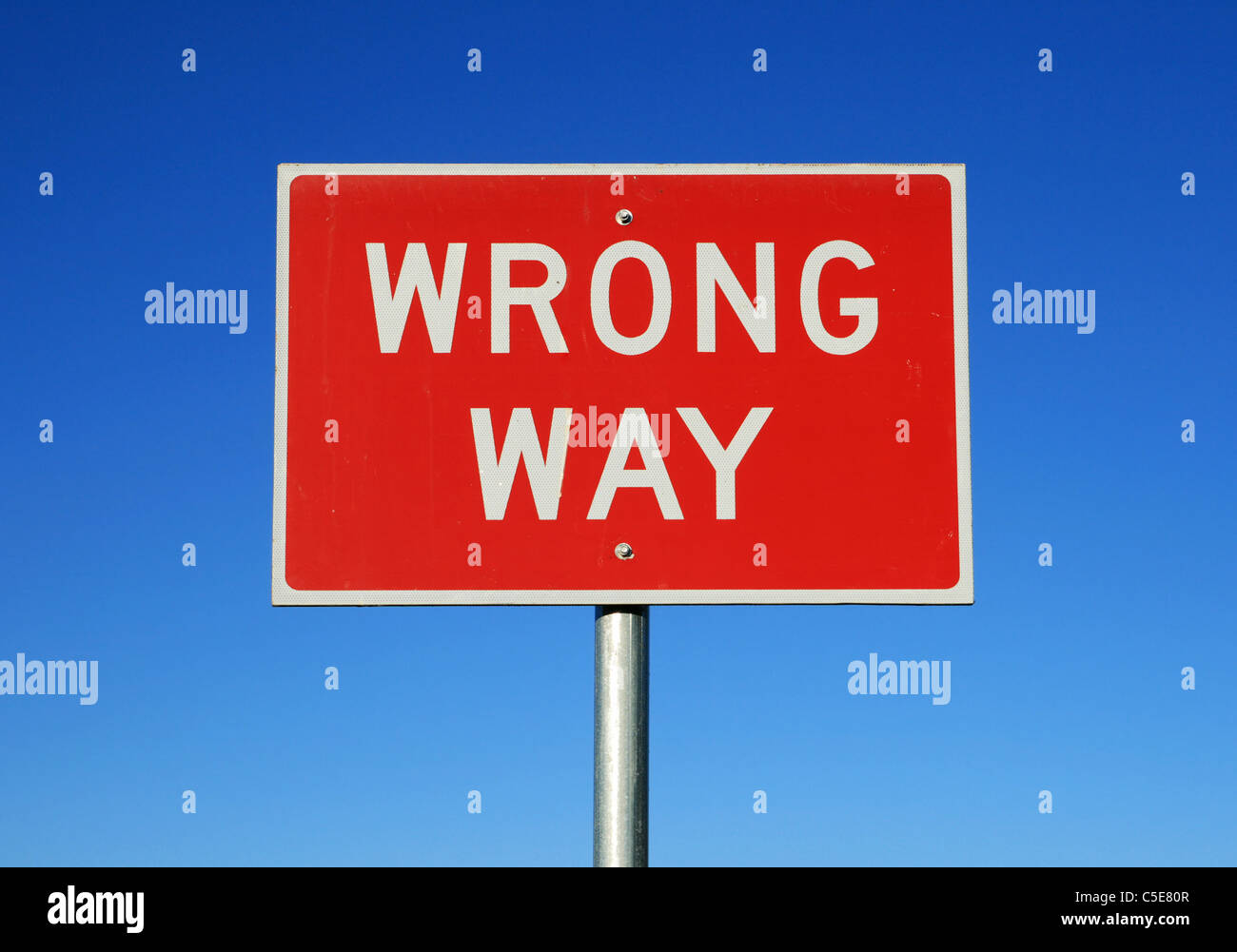 wrong way road sign on a blue sky background - Stock Image