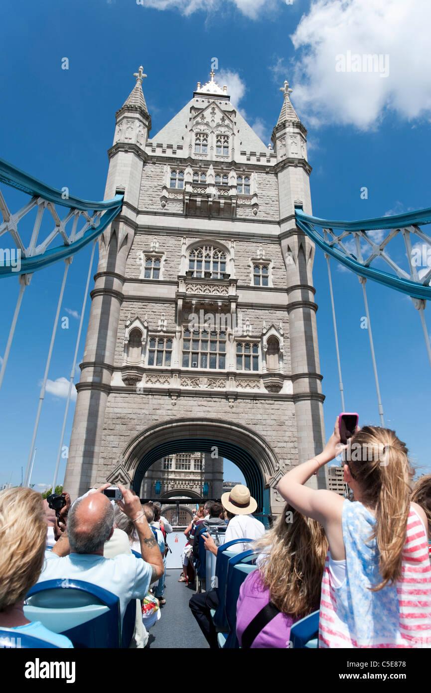 Tourists on open top double decker Original London tour bus crossing Tower Bridge, London, UK - Stock Image