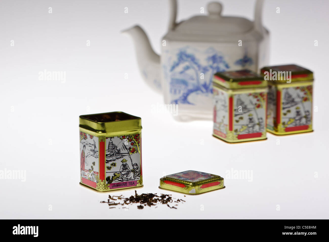 Tins of jasmine tea with a traditional willow pattern chines teapot against a plain white background - Stock Image
