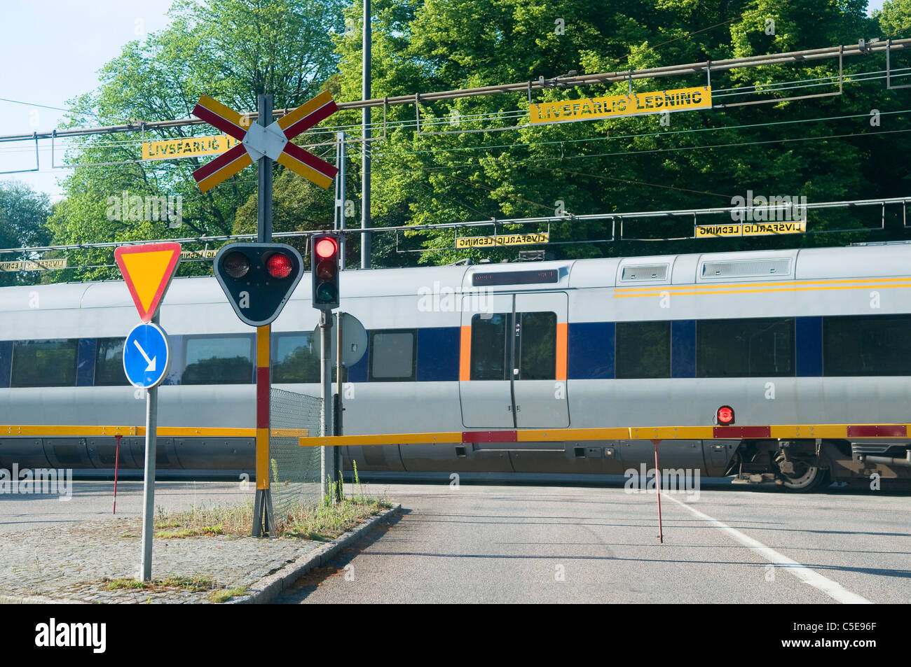 Passenger train passing over railroad crossing with traffic signs in foreground Stock Photo