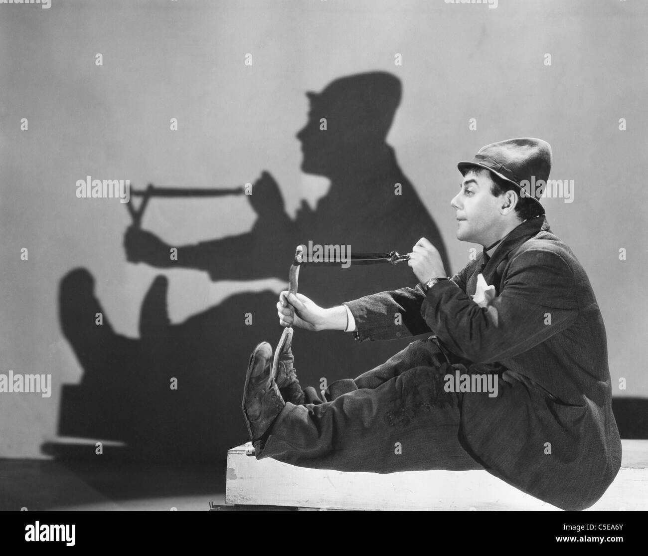 Man aiming slingshot - Stock Image