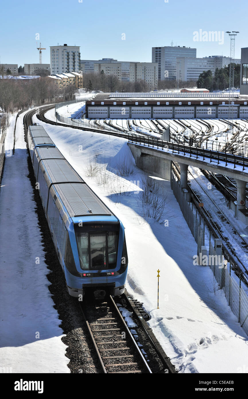 High angle view of underground trains with suburban buildings in the background - Stock Image