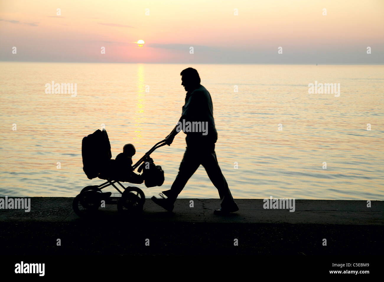 Side view of a silhouette man with pram walking by the peaceful sea at sunset - Stock Image