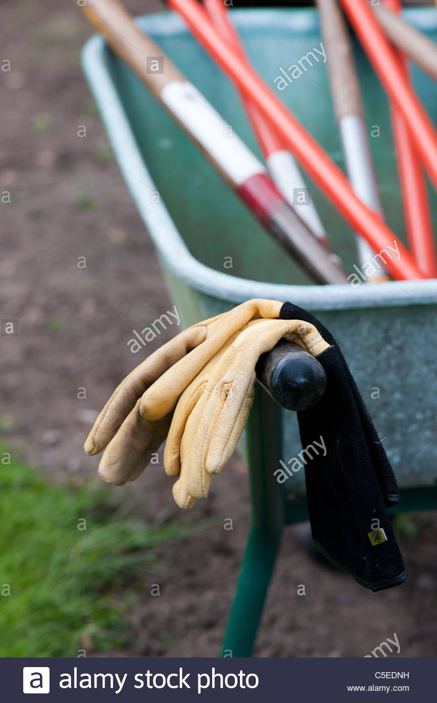 Gardening Gloves with tools on a wheelbarrow - Stock Image