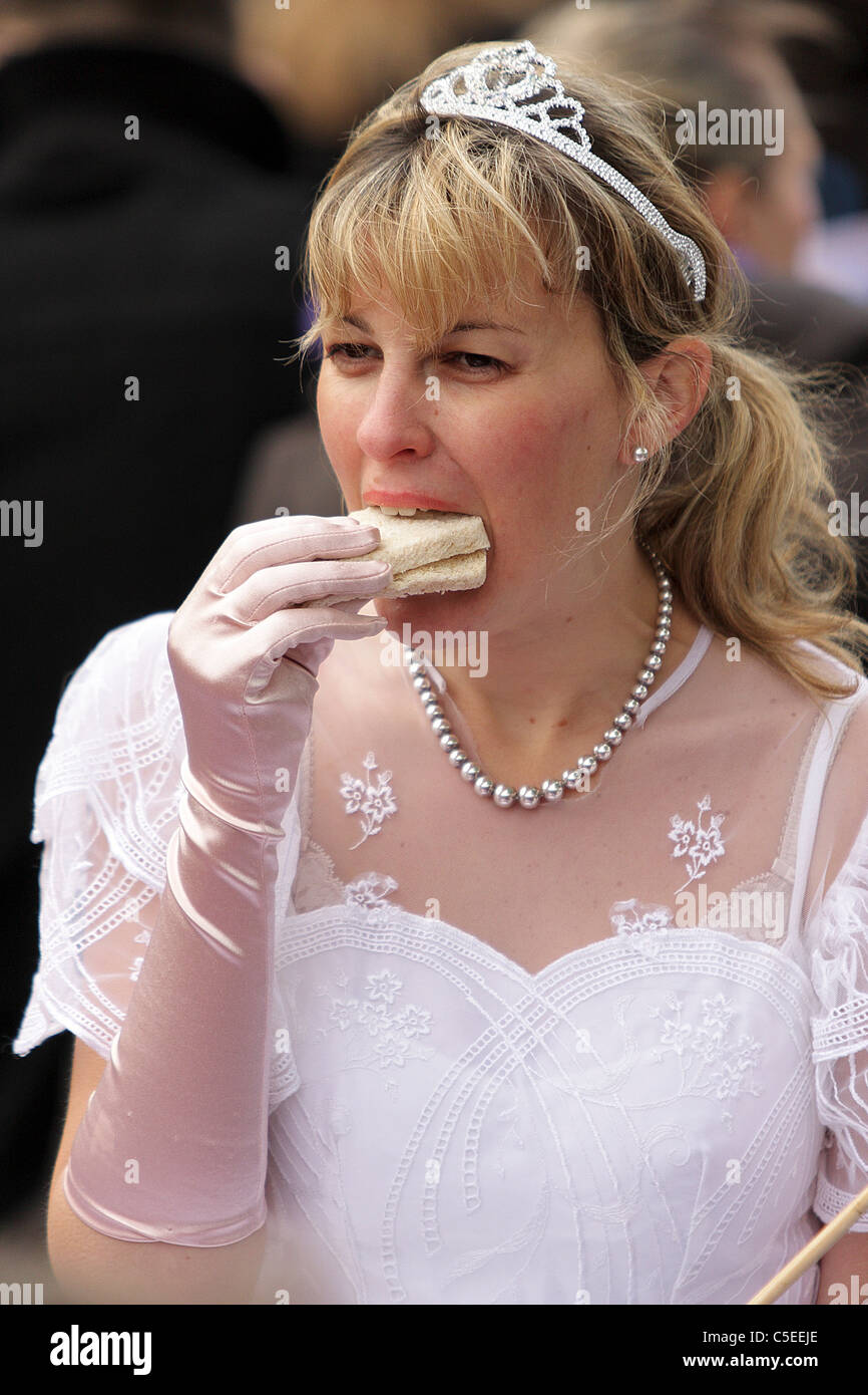 THE ROYAL WEDDING DAY 2011, an attractive blond haired female enjoys her sandwich in Green Park dressed as a Princess. - Stock Image