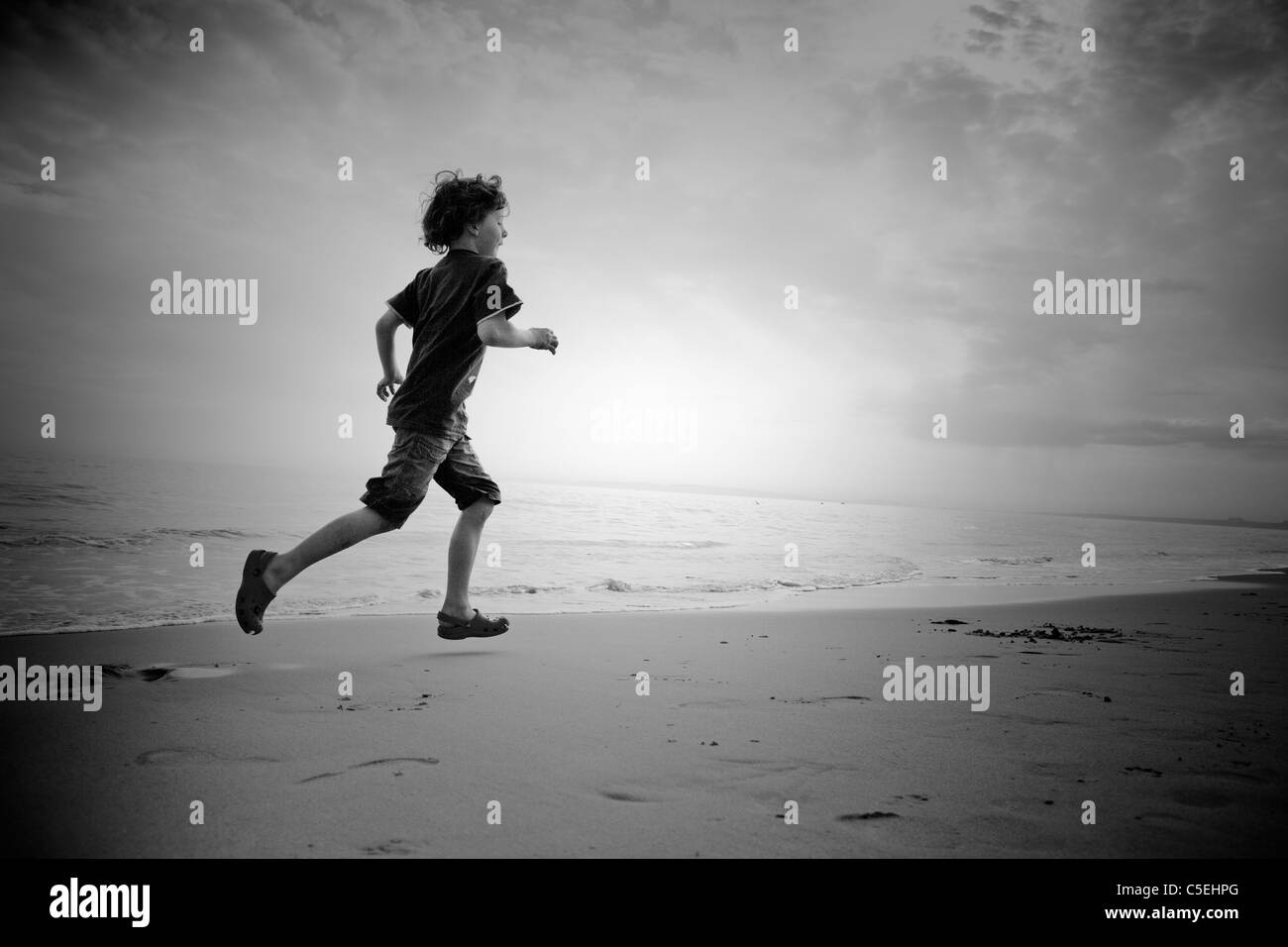 Boy runs on a beach - Stock Image