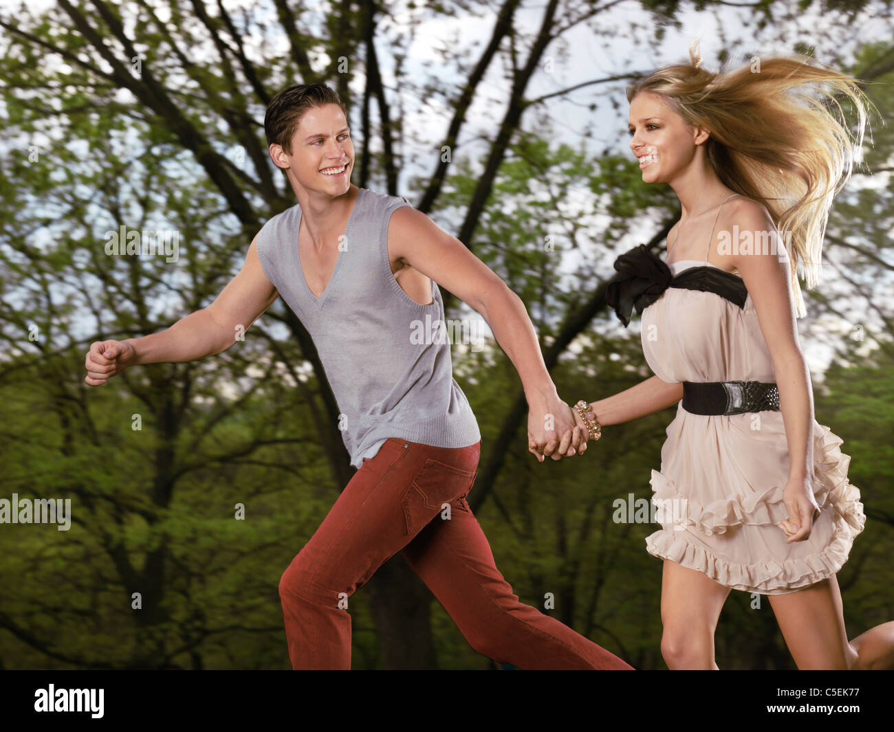 Young happy romantic couple running together holding their hands - Stock Image