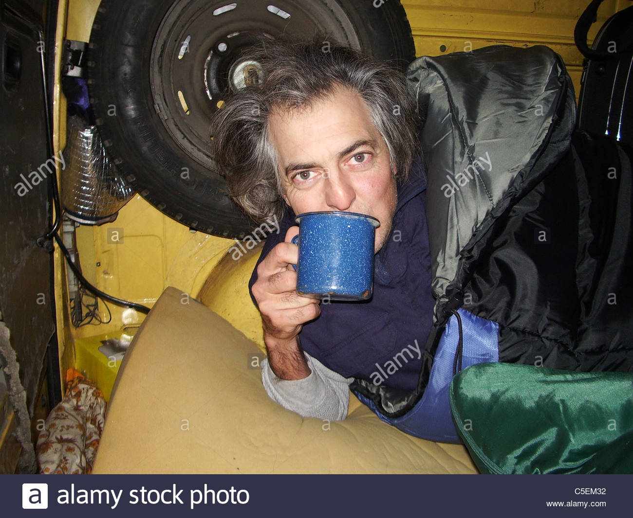 Camping equipment used by explorer Kypros in Africa - mug of tea inside a vehicle while wearing two sleeping bags Stock Photo