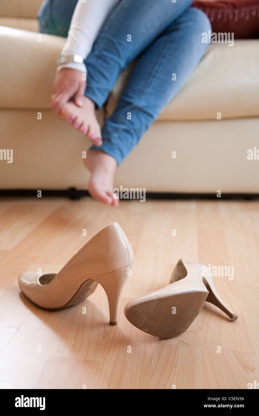 Young woman sat at home rubbing her feet after taking off her high heels Stock Photo