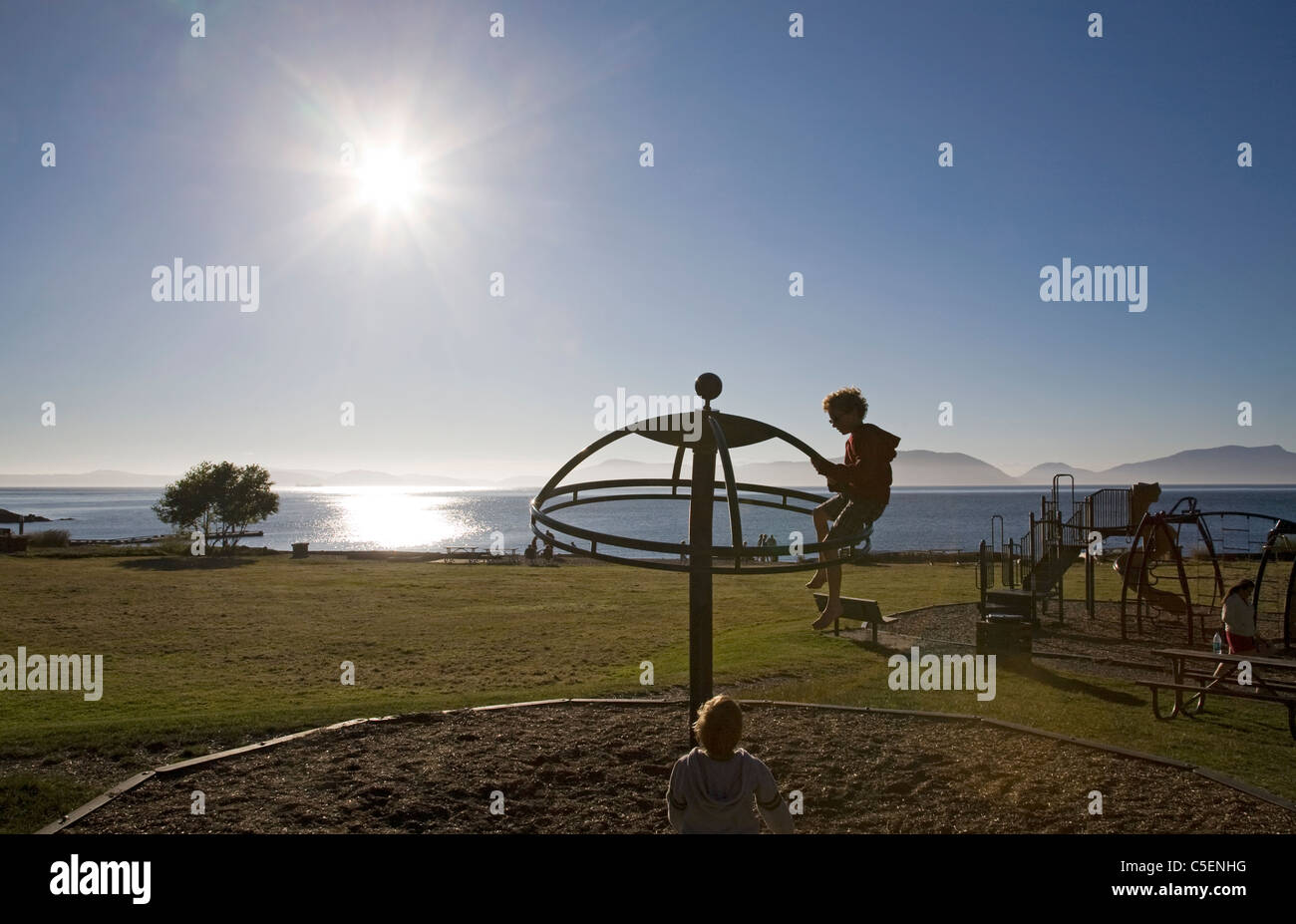 Two boys on a swing in a community park playground, Washington coast. - Stock Image