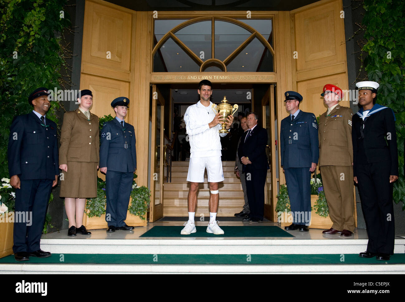 Novak Djokovic (SRB) on the club house front steps with the trophy after victory at the 2011 Wimbledon Tennis Championships - Stock Image