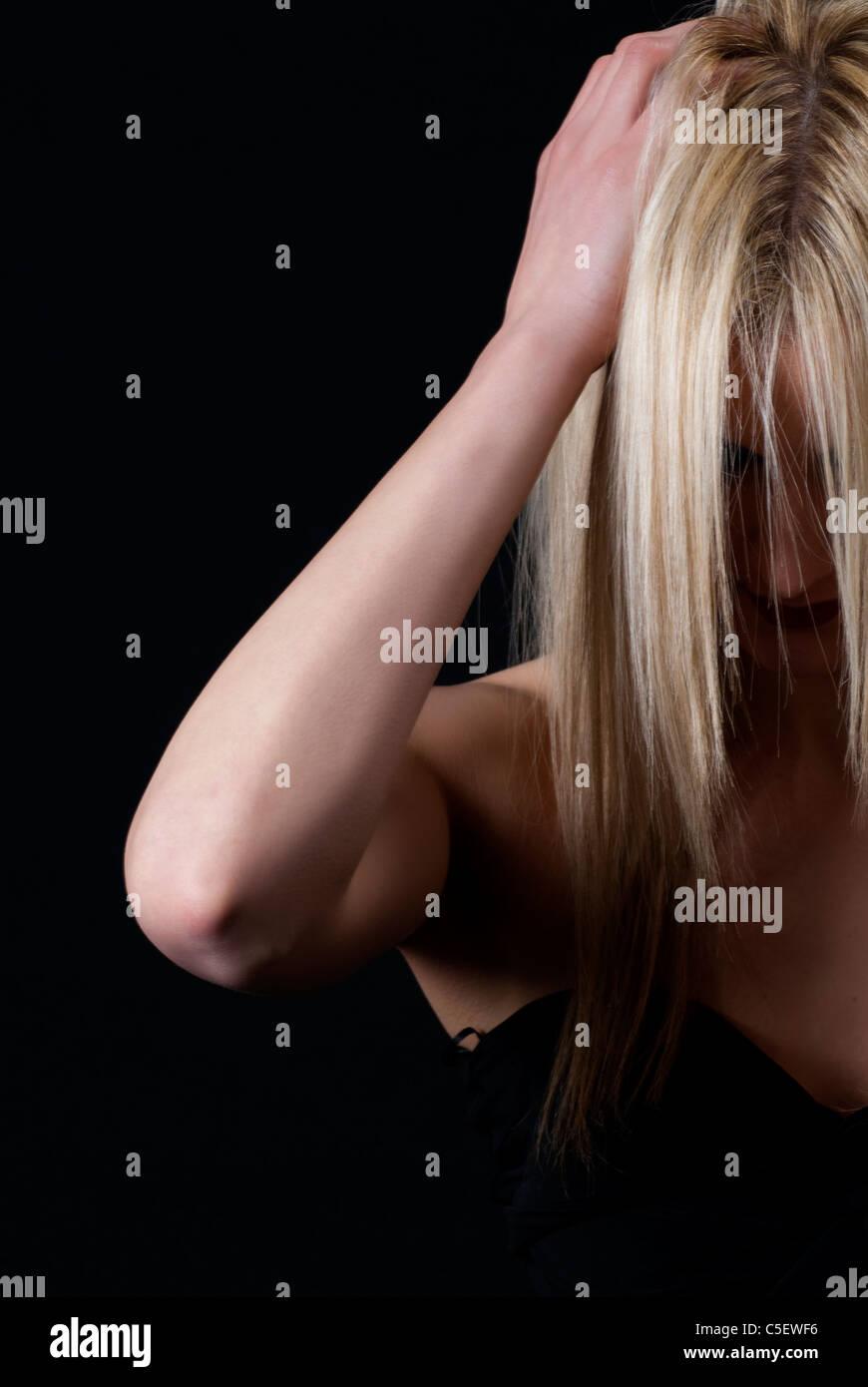 Depressed woman head in hands - Stock Image