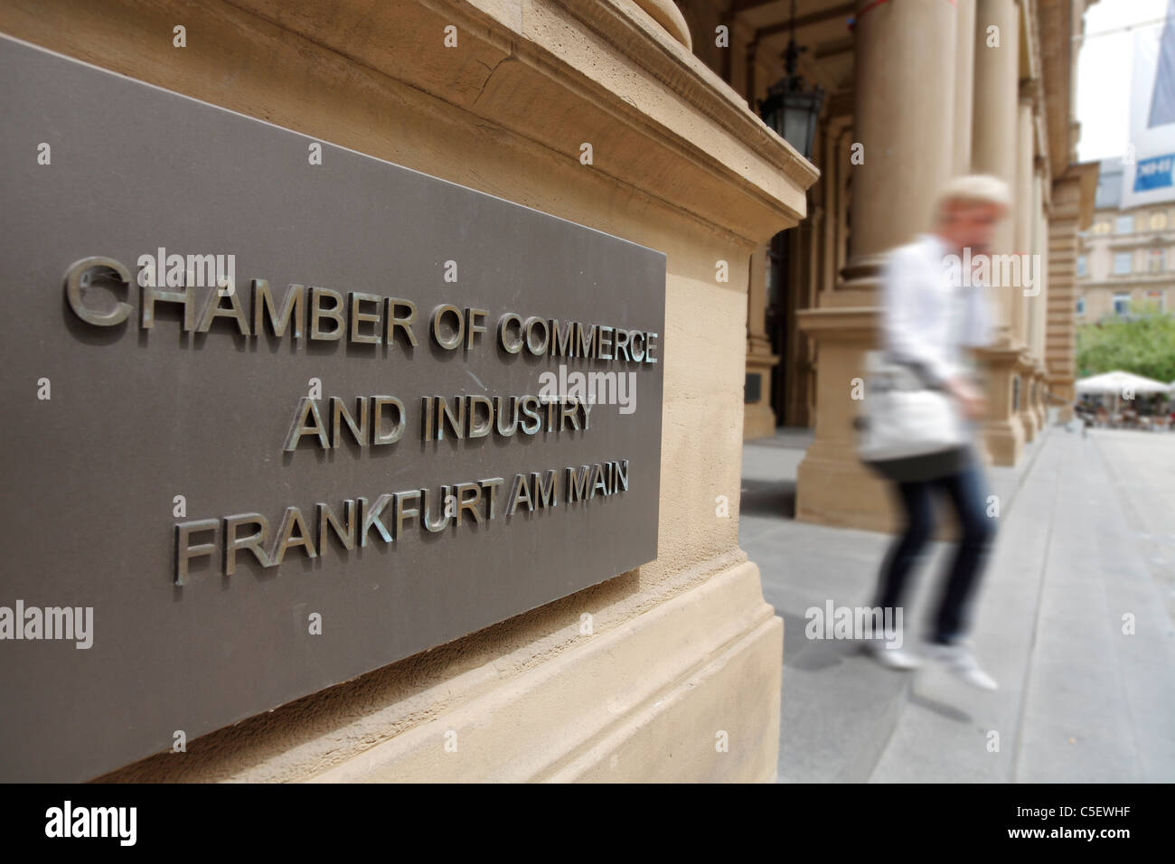 business woman leaving Chamber of Commerce and Industry Frankfurt am Main (sign) and Frankfurt Stock Exchange, Frankfurt,Germany - Stock Image