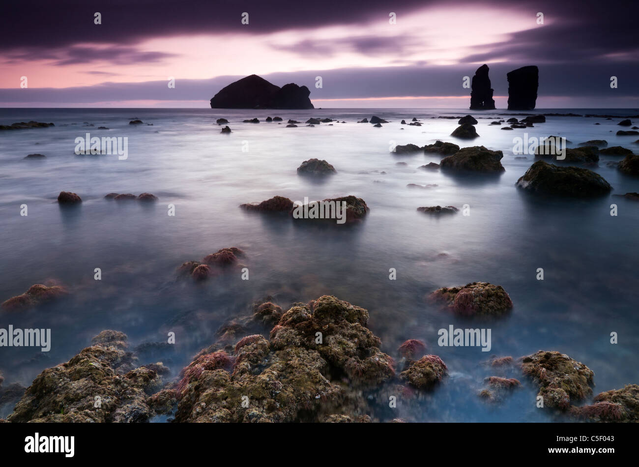 Waterscape on sunset with volcanic islets - Stock Image