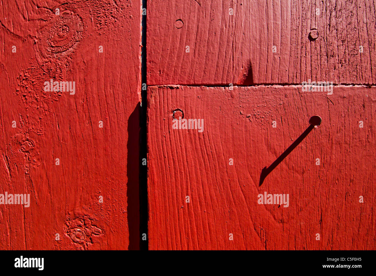 The shadow of a nail against painted red barn wood. - Stock Image