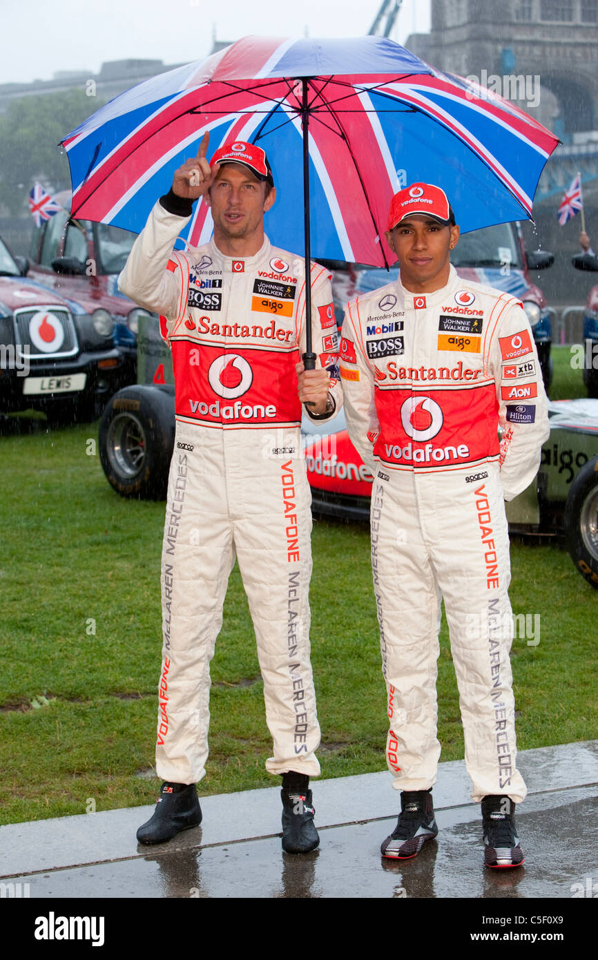Former Formula 1 world champions Jenson Button and Lewis Hamilton attend a photocall in the pouring rain in London - Stock Image